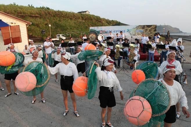지난해 제주국제관악제 기간 제주시 한경면 고산리 자구내포구에서 해녀들과 외국 관악단의 협연 모습. 조직위원회 제공