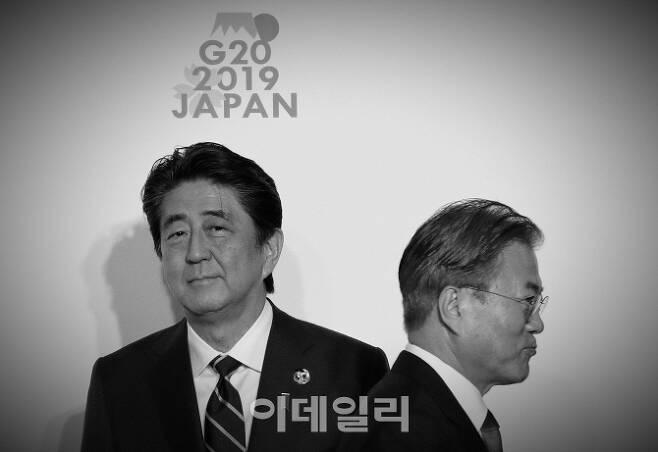 △6월 29일 일본 오사카에서 열린 주요20개국·지역(G20) 정상회담을 참여한 문재인 대통령이 아베 신조 일본 총리와 악수한 뒤 지나가고 있다.[사진=AFP제공]