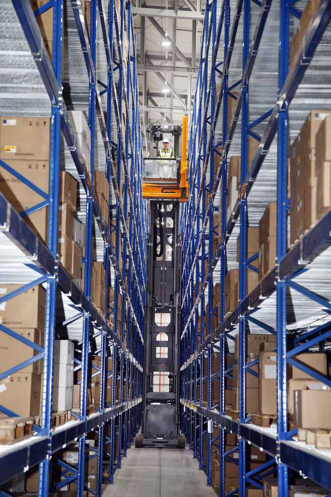 An automated forklift truck moves parts to an 11.5-meter-high storage shelf in a very narrow aisle. (Mercedes-Benz Korea)
