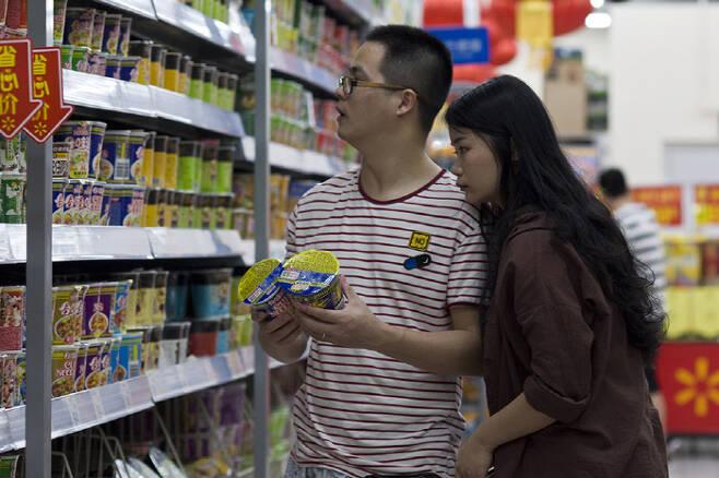 중국의 한 슈퍼마켓 진열대에서 남녀가 라면을 고르고 있다.                                                                                                     사진 남방주말