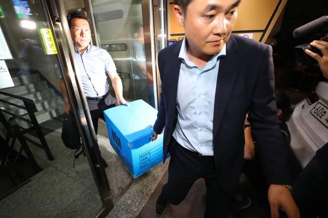 지난달 27일 저녁 서울 강남구의 한 빌딩에서 검찰 관계자들이 조국 법무부 장관 후보자 가족이 투자한 사모펀드 운용사 코링크프라이빗에쿼티 사무실의 압수수색을 마친 뒤 압수품들을 차량으로 옮기고 있다. 연합뉴스