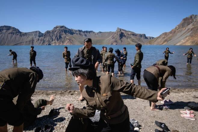북한 학생들이 지난 11일 신발을 벗고 백두산 천지로 들어가고 있다. [AFP=연합뉴스]