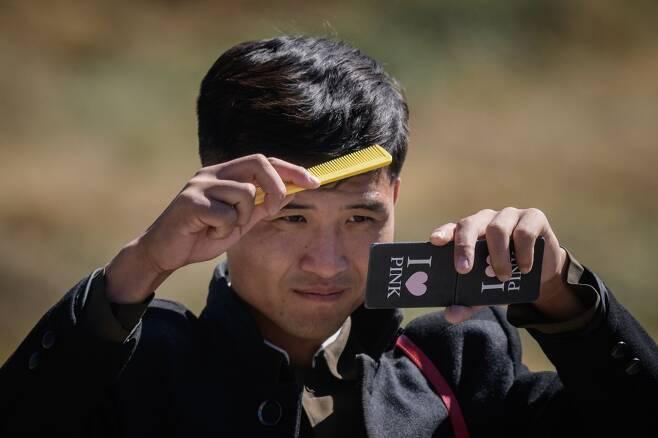 """지난 11일 백두산 천지를 방문한 한 북한 학생이 친구들과 물장난을 한 후 머리를 빗고 있다. """"나는 핑크를 좋아한다""""는 영문이 눈에 띈다. [AFP=연합뉴스]"""