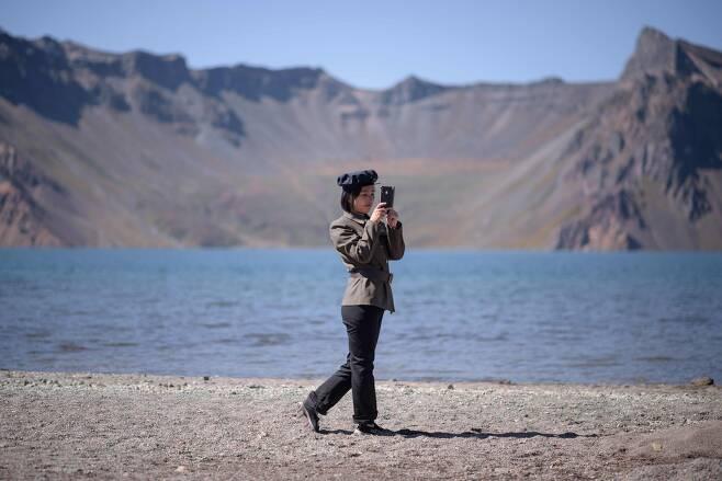한 북한 학생이 스마트폰으로 백두산 천지를 카메라에 담고 있다. [AFP=연합뉴스]