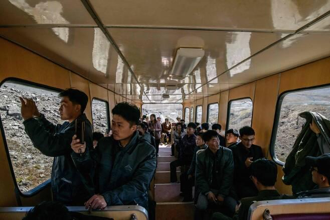 북한 주민들이 지난 11일 백두산 정상으로 가는 케이블 기차를 타고 주변 풍경을 카메라에 담고 있다. [AFP=연합뉴스]