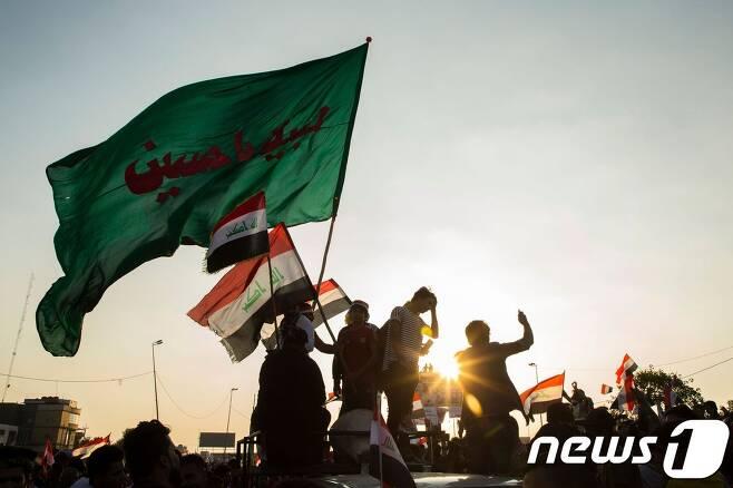 1일(현지시간) 이라크 수도 바그다드에서 이라크 국기를 든 채 시위를 벌이고 있는 반정부 시위대. © AFP=뉴스1
