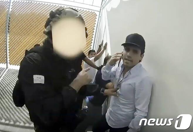 멕시코 특경대에 체포된 마약왕 구스만의 아들 오비디오의 모습. 전화로 공격을 멈추라 지시했지만 조직원들의 거센 저항이 지속되자 경찰은 그를 다시 풀어주고 말았다. 당시 체포 작전에 나섰던 경찰이 갱단에 암살 당했다. © AFP=뉴스1