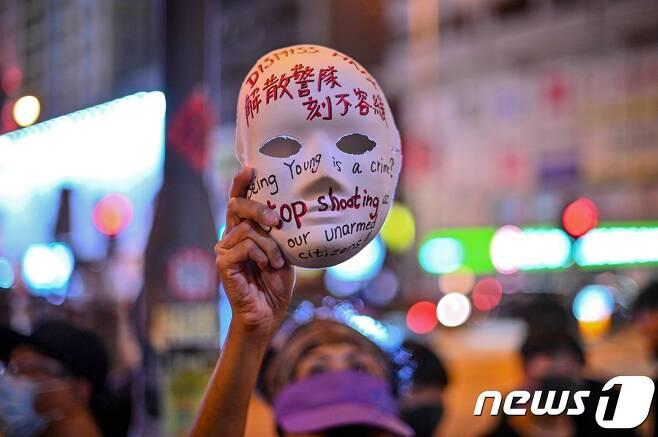 지난 10월5일 홍콩 몽콕 경찰서 인근에 시위대가 모이자 한 여성이 시위대의 마스크 착용을 금지하는 복면금지법 시행을 규탄하며 구호가 적힌 마스크를 들고 있다.  © AFP=뉴스1