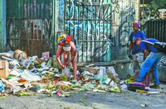 베네수엘라 수도 카라카스에서 한 시민이 음식을 찾아 쓰레기 통을 뒤지고 있다. [ 연합뉴스]