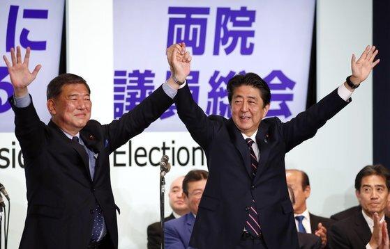지난해 9월 자민당 총재 경선에서 3연임에 성공한 아베 신조 총리와 경쟁자였던 이시바 시게루 전 간사장이 함께 인사를 하고 있다. [EPA=연합뉴스]