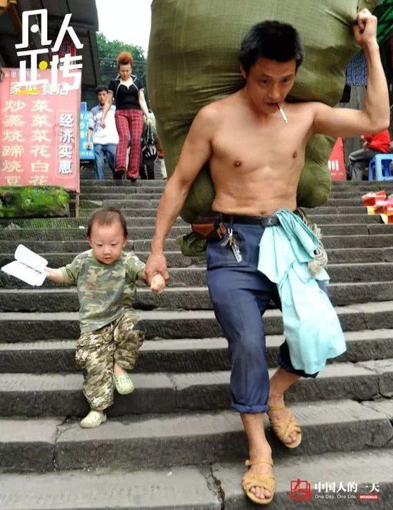 충칭시 차오톈먼 도매시장의 짐꾼 란광후이가 2010년 등엔 짐을, 오른손으론 세 살 아들의 손목을 잡고 계단을 내려오고 있다. [중국 인민망 캡처, 쉬캉핑]