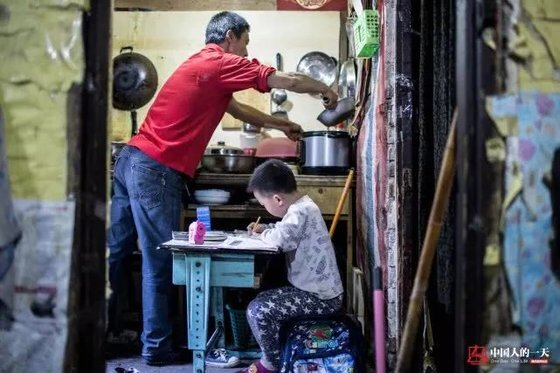 란광후이의 아들은 판자촌 거주 시절 부엌 등불 아래 숙제를 해야 했다. [중국 인민망 캡처, 쉬캉핑]