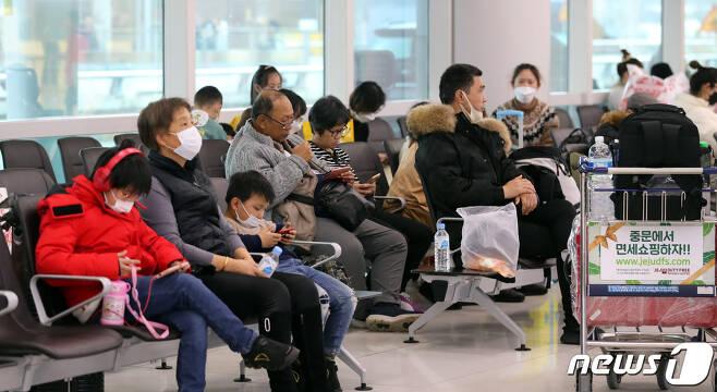 23일 오후 제주국제공항 국제선 출국장에 마스크를 낀 중국인 관광객들이 앉아 있다. 24일부터 시작되는 춘절 기간 동안 3만 명에 육박하는 중국인 관광객들이 제주를 찾는다. 2020.1.23 /뉴스1© News1