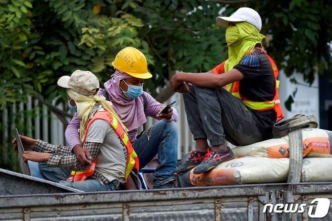 지난달 31일 캄보디아 수도 프놈펜에서 신종 코로나바이러스 감염을 막기 위해 마스크를 착용하고 있는 건설 노동자들. © AFP=뉴스1