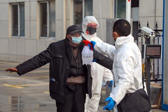 지난 3일 중국 후베이성 우한시가 격리포인트로 지정된 호텔에서 감염 의심자로 분류돼 병원으로 향하는 한 남성에게 방호복을 입은 현지 당국 관계자가 소독약을 뿌리고 있다. [EPA=연합뉴스]