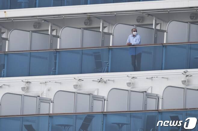 14일 요코하마항에 강제 격리된 채 정박해 있는 다이아몬드 프린세스호에서 마스크를 쓴 승객이 발코니에 나와 있다. © AFP=뉴스1 © News1 우동명 기자