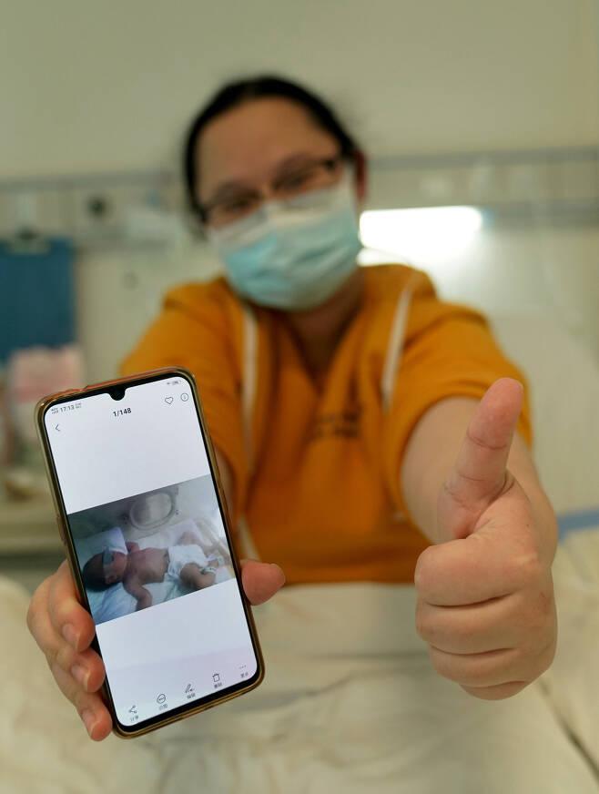 2월18일 우한의 한 병원에서 코로나19로 투병 중인 한 여성이 병상에서 낳은 아기 사진을 보여주고 있다. 아기는 건강 상태가 양호하다.