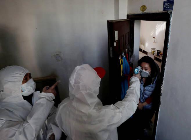 방역복을 입은 방역 관계자가 2월17일 우한의 주거지역을 집집마다 돌며 주민들의 체온을 재고 있다.
