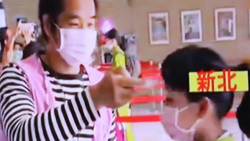 등교하는 학생의 체온 측정하는 학교 관계자(왼쪽) [대만 EBC 캡처]