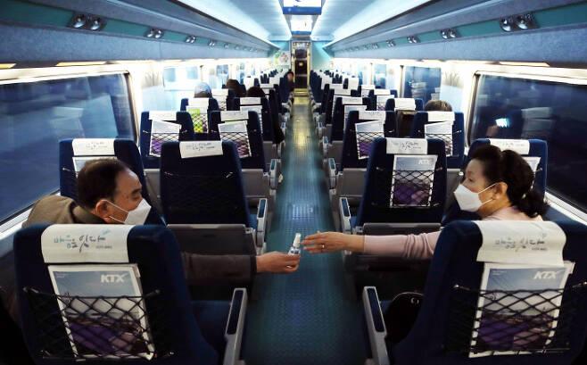 열차 안에서 떨어져 앉은 부부 한국철도공사(코레일)가 코로나19 확산 방지를 위해 모든 승객에 대해 창가 좌석을 우선 배정하기로 한 첫날인 3일 서울역에서 부산으로 가는 KTX 열차 안에서 한 부부가 떨어져 앉은 채 손소독제를 건네고 있다.  연합뉴스
