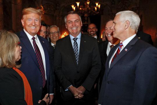 자이르 보우소나루(가운데) 브라질 대통령의 미국 방문을 수행하고 귀국한 뒤 신종 코로나바이러스 감염증(코로나19) 확진 판정을 받은 대통령실 커뮤니케이션국의 파비우 바인가르텐 국장이 지난 7일 도널드 트럼프(왼쪽 두번째) 미국 대통령과 함께 플로리다주의 만찬장에 서있는 모습. 트럼프 대통령 뒤에 얼굴 일부가 가려진 인물이 바인가르텐 국장이다.    [플로리다=AP 연합뉴스]