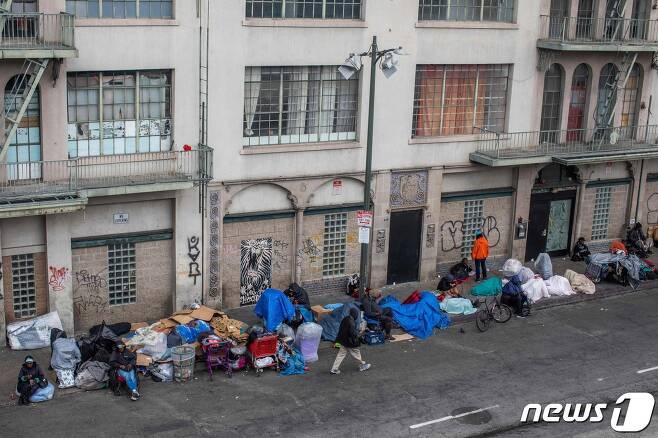 19일(현지시간) 코로나19 확산 속 캘리포니아주 로스앤젤레스 중심가의 건물 앞에 노숙자들이 모여 있다. © AFP=뉴스1 © News1 우동명 기자