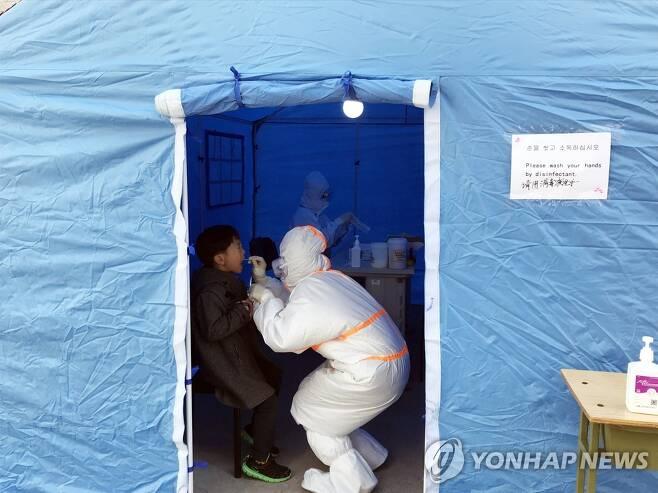 중국 코로나19 검사소 (베이징=연합뉴스) 김진방 특파원 = 중국 베이징시가 17일부터 2월 이후 해외 입국자 전원을 대상으로 신종 코로나바이러스 감염증(코로나19) 핵산 검사를 실시하고 있다. 사진은 베이징 차오양(朝陽)구 왕징 위생서비스센터에 설치된 검사소에서 검사 대상자가 검사받는 모습. 2020.3.17 chinakim@yna.co.kr
