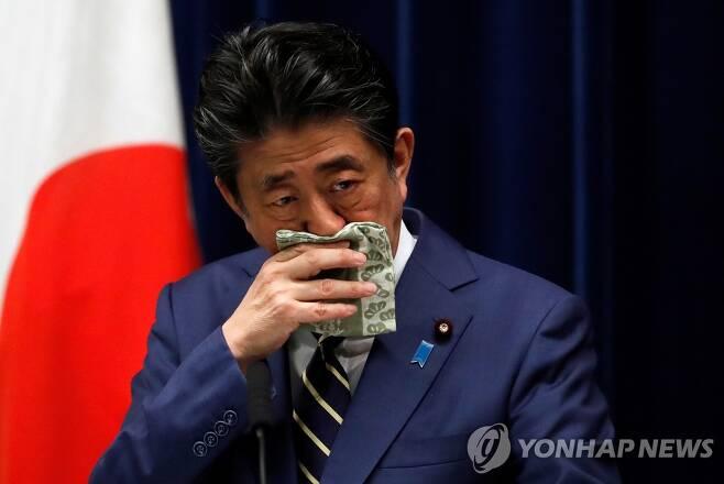 (도쿄 로이터=연합뉴스) 아베 신조 일본 총리가 28일 도쿄 총리관저에서 기자회견을 하는 도중 손수건으로 코를 닦고 있다. 2020.3.31
