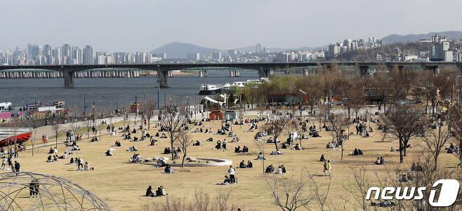 27일 오후 서울 여의도 한강공원에서 시민들이 봄날씨를 만끽하고 있다. 이날 정부는 이번 주말 야외활동을 자제하고 사회적 거리두기에 동참해 줄 것을 호소했다. 2020.3.27/뉴스1 © News1 박지혜 기자