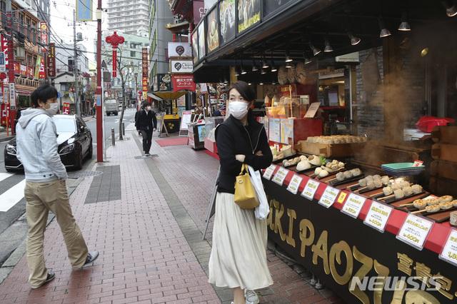 [요코하마=AP/뉴시스]지난달 31일 신종 코로나바이러스 감염증(코로나19) 확산을 막기 위해 마스크를 쓴 한 여성이 일본 도쿄 인근 요코하마의 차이나타운 상가에서 음식을 기다리고 있다. 2020.03.31.