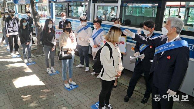 11일 부산지하철 2호선 동의대역 출구 앞에서 공순진 동의대 총장(오른쪽)과 대학 홍보대사인 학생들이 학생들을 대상으로 발열 검사를 실시했다. 부산=박경모 기자 momo@donga.com
