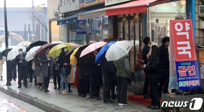 마스크 5부제 시행 이틀째인 10일 서울 강남구 테헤란로의 한 약국에서 우산을 쓴 시민들이 마스크를 사기 위해 줄을 서고 있다. 2020.3.10/뉴스1 © News1 구윤성 기자