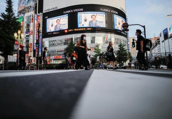 지난 14일 도쿄 신주쿠 빌딩에 설치된 대형 모니터를 통해 아베 신조 일본 총리의 긴급사태 선언 일부 해제 발표가 생중계되고 있다. 로이터 뉴스1