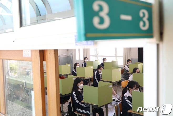 고3 학생들의 등교 수업이 시작된 20일 대구의 한 여고 교실에서 마스크를 쓴 학생들이 칸막이 너머로 수업을 듣고 있다.  사진은 기사 내용과 직접적 관련 없음. 2020.5.20/뉴스1 © News1 공정식 기자