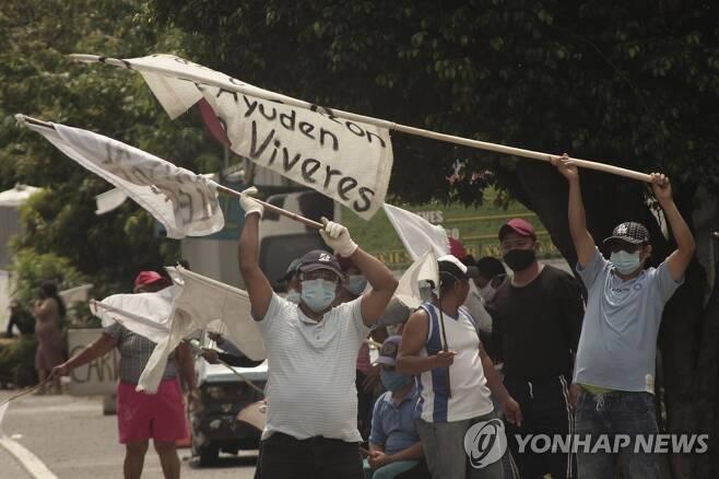 엘살바도르 빈민들이 지나는 차량을 향해 식량 지원을 호소하는 흰 깃발을 흔들고 있다. [AP=연합뉴스]