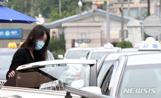 [서울=뉴시스] 박미소 기자 = 정부가 오는 26일부터 승객이 버스나 택시를 탈 때 운송사업자와 운수종사자가 마스크를 착용하지 않을 경우 관할 시·도지사가 개선 조치를 내리도록 한 25일 오후 서울 용산구 서울역 인근 택시 정류장에서 시민들이 마스크를 쓰고 택시에 탑승하고 있다. 2020.05.25.  misocamera@newsis.com