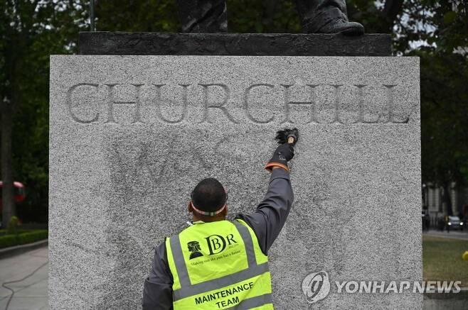 시설 보수 담당자가 처칠 동상에 적힌 낙서를 지우고 있다. [AFP=연합뉴스]