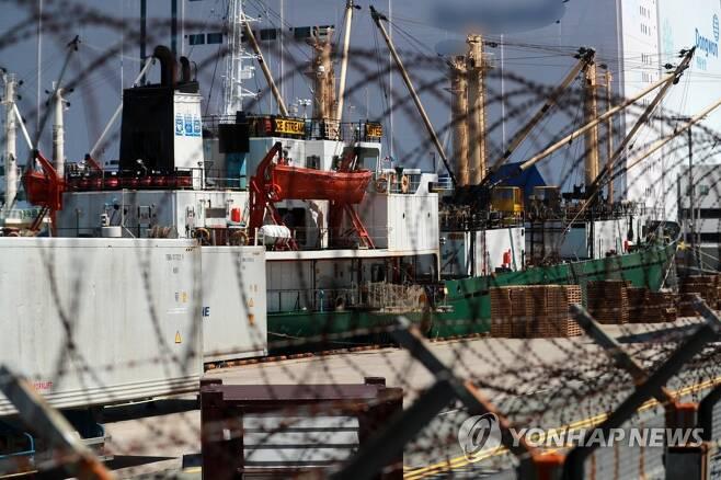 선원 집단 감염 발생한 러시아 선박 (부산=연합뉴스) 손형주 기자 = 23일 부산 감천항에 정박 중인 러시아 국적 냉동 화물선인 A호(3천401t)에서 한 승선원이 휴대전화기를 들고 있다. 이 배 선장 등 21명 중 16명이 코로나19 양성 판정을 받았다. 부산시 보건당국은 러시아 국적 냉동화물선 확진자와 밀접 접촉한 사람이 현재까지 61명으로 집계됐다고 밝혔다. 2020.6.23 handbrother@yna.co.kr