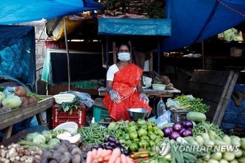 마스크와 장갑을 착용한 채 손님을 기다리는 인도 뉴델리 시장의 한 상인. [로이터=연합뉴스]