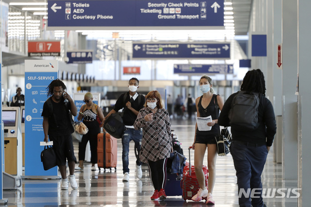 [시카고=AP/뉴시스]지난 6월16일 시카고 오헤어 국제공항에서 마스크를 착용한 여행객들이 이동하는 모습. 2020.07.03.