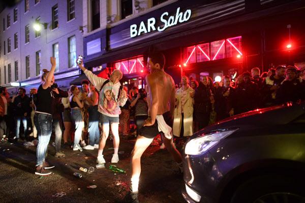 영국 런던 소호 거리에서 술에 취한 시민들이 차량 통행을 막아선 채 춤을 추고 있다/사진=AFP
