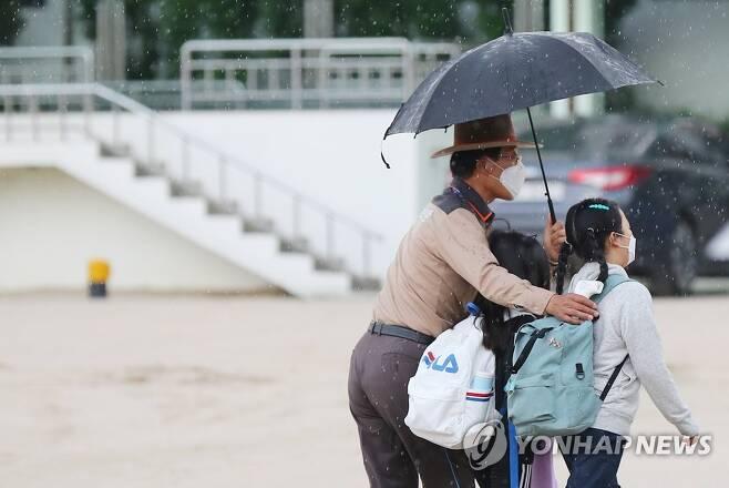 소나기 속 따스한 등굣길 [연합뉴스 자료사진]
