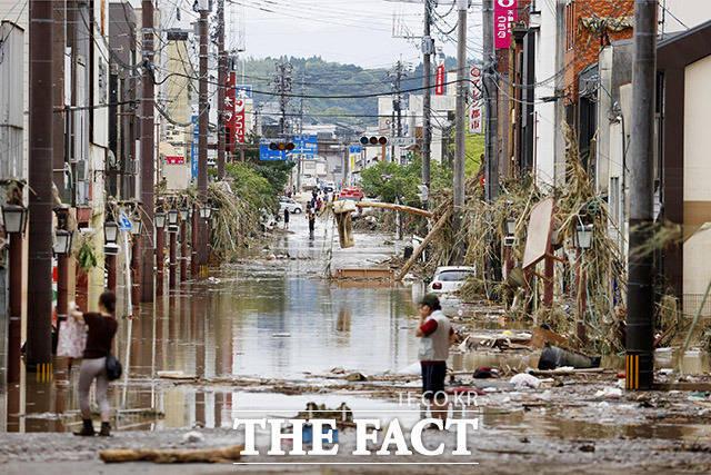 일본 규슈 구마모토현 일대에 최대 시간당 100mm 가까운 폭우가 쏟아지면서 홍수와 침수 등으로 수십명이 숨진 가운데 지난 4일 히토요시 시내에서 주민들이 물건 등을 챙기며 현장을 수습하고 있다. /히토요시(일본)=AP.뉴시스