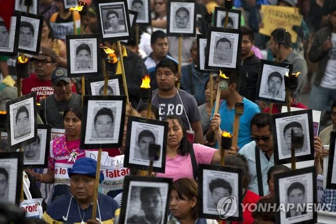 멕시코 실종 교대생들의 사진을 들고 시위하는 유족과 시민들 [AP=연합뉴스 자료사진]