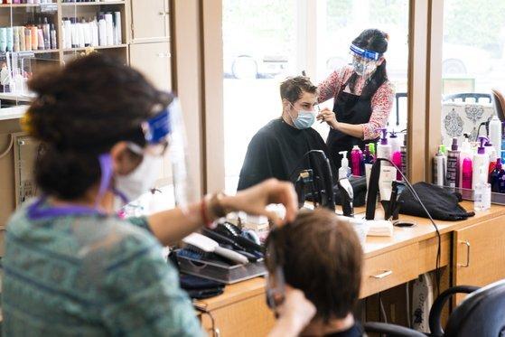 미국 워싱턴 DC의 한 미용실에서 미용사들이 마스크와 페이스실드를 착용하고 머리 손질을 하고 있다. [EPA=연합뉴스]