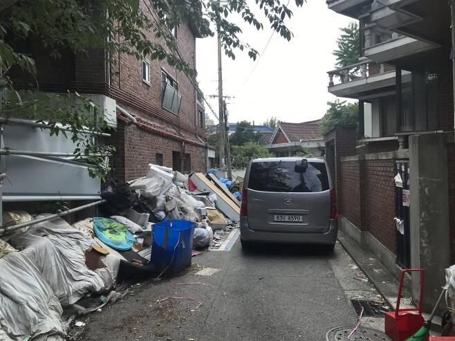 사랑제일교회로 들어오는 골목이 차량과 쓰레기로 막혀 있다. 좌측 상단에 보이는 CCTV로 교회 측은 오고가는 이들을 감시하고 있었다./이정현 기자