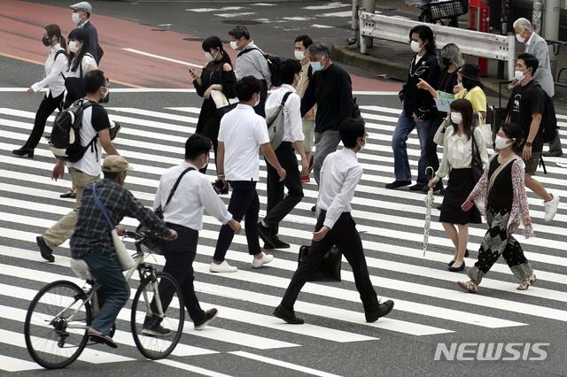 [도쿄=AP/뉴시스]지난 16일 일본 도쿄 거리의 한 횡단보도에서 신종 코로나바이러스 감염증(코로나19) 예방을 위해 마스크를 쓴 시민들이 걸어가고 있다. 2020.07.17.