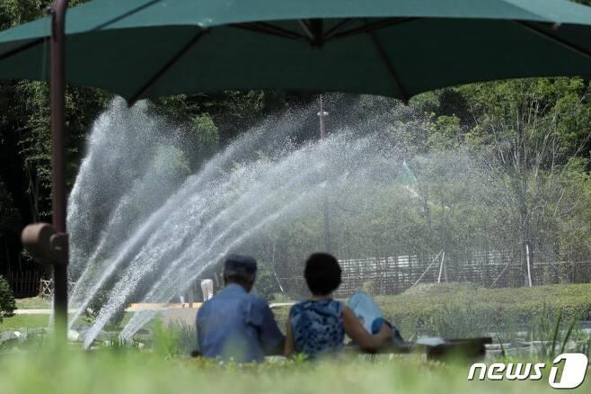 (울산=뉴스1) 윤일지 기자 = 울산지역에 무더운 날씨를 보인 21일 울산 태화강 국가정원 오산못에서 그늘 밑에 앉은 시민들이 분수대에서 시원하게 뿜어져 나오는 물줄기를 바라보고 있다. 2020.7.21/뉴스1