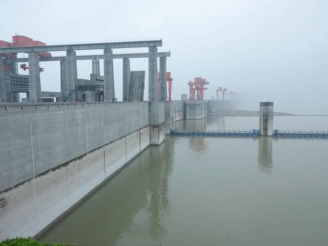 반대 끝이 보이지 않는 싼샤댐 (이창[중국 후베이성]=연합뉴스) 차대운 특파원 = 21일 중국 후베이성 이창시에 있는 싼샤댐의 수위가 높은 곳까지 올라와 있다. 댐 상단의 회색 부분과 상아색 부분을 가로로 나누는 선이 최고 수위인 175m를 표시하는 것으로 추정된다. 2020.7.22  cha@yna.co.kr  (끝)