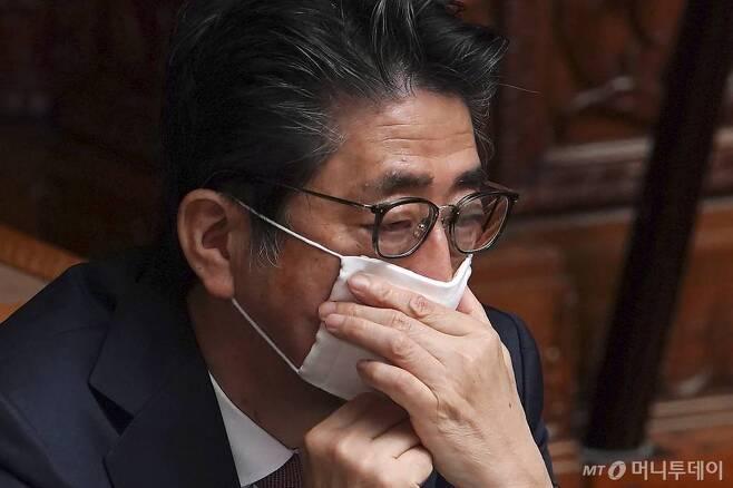 [도쿄=AP/뉴시스]신종 코로나바이러스 감염증 예방을 위해 마스크를 쓴 아베 신조 일본 총리가 3일 일본 도쿄에서 열린 국회 상원 본회의에 참석해 마스크를 매만지고 있다. 아베 총리는 지난 1일 코로나19 정부 대책 본부 회의에서 가구당 천 마스크 2개를 배포하겠다는 방침을 발표했다가 거센 비난에 직면한 바 있다. 2020.04.03.